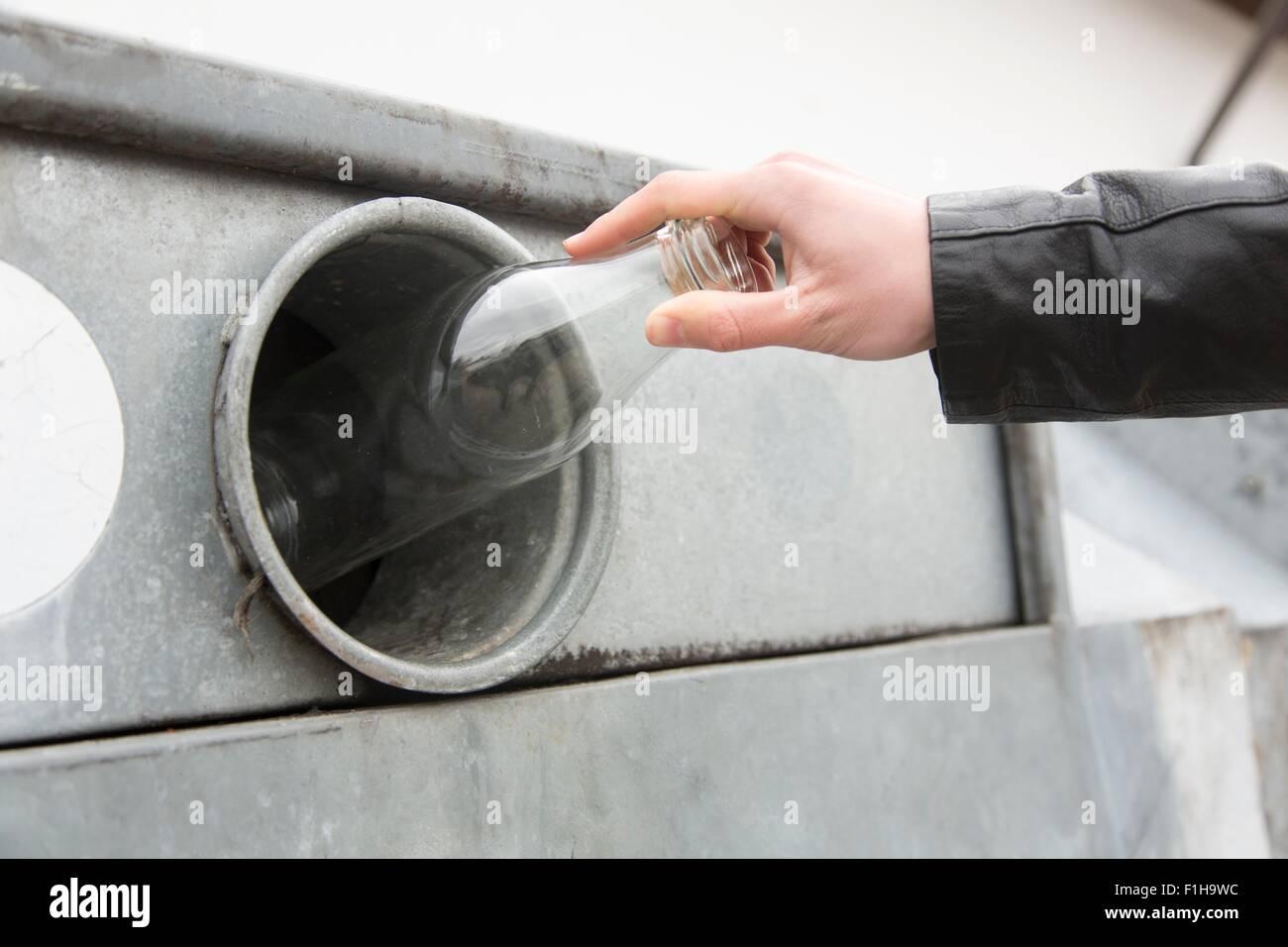 Persona il riciclaggio bottiglia di latte in bottiglia bank Immagini Stock