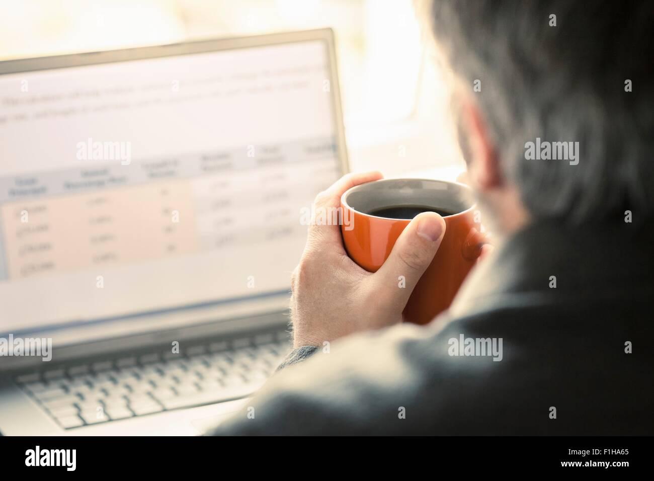 Sulla spalla vista dell uomo la navigazione portatile a scrivania Immagini Stock