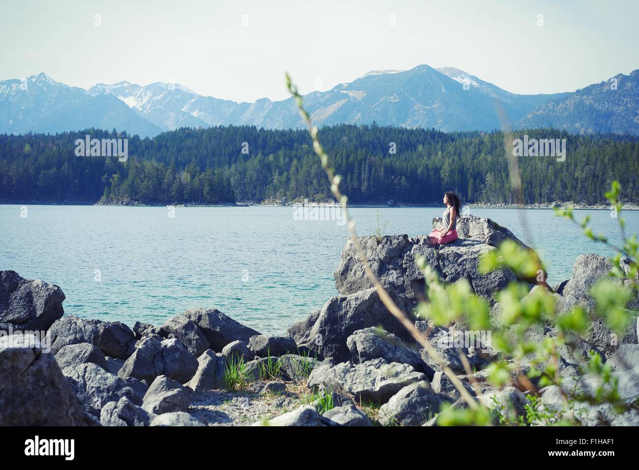 Metà donna adulta, seduti su una roccia in posizione di yoga Immagini Stock