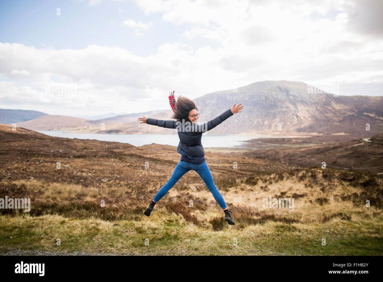 Metà donna adulta in montagna facendo star jump, Isola di Skye, Ebridi, Scozia Immagini Stock