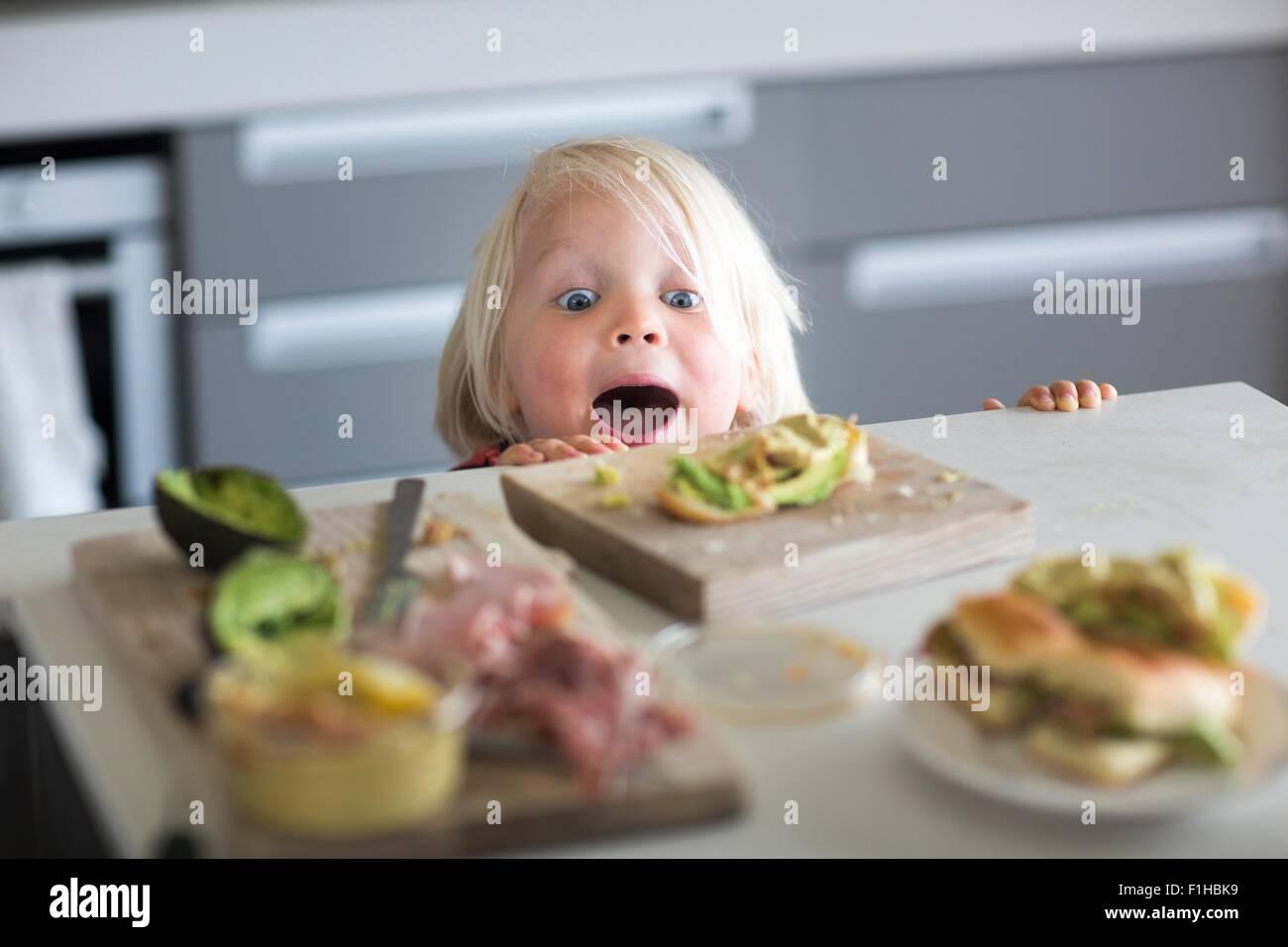 Ragazzo peeking su banco di cucina Immagini Stock