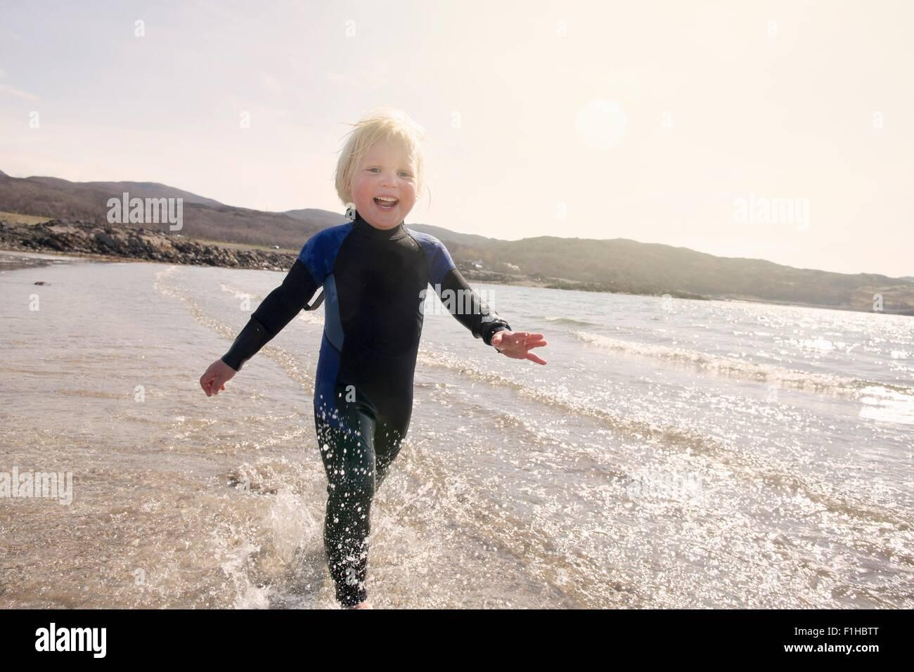 Ragazzo in esecuzione sulla spiaggia, Loch Eishort, Isola di Skye, Ebridi, Scozia Immagini Stock