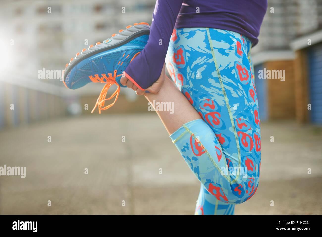Vista ritagliata della donna la piegatura della gamba e stretching prima di esercizio Immagini Stock