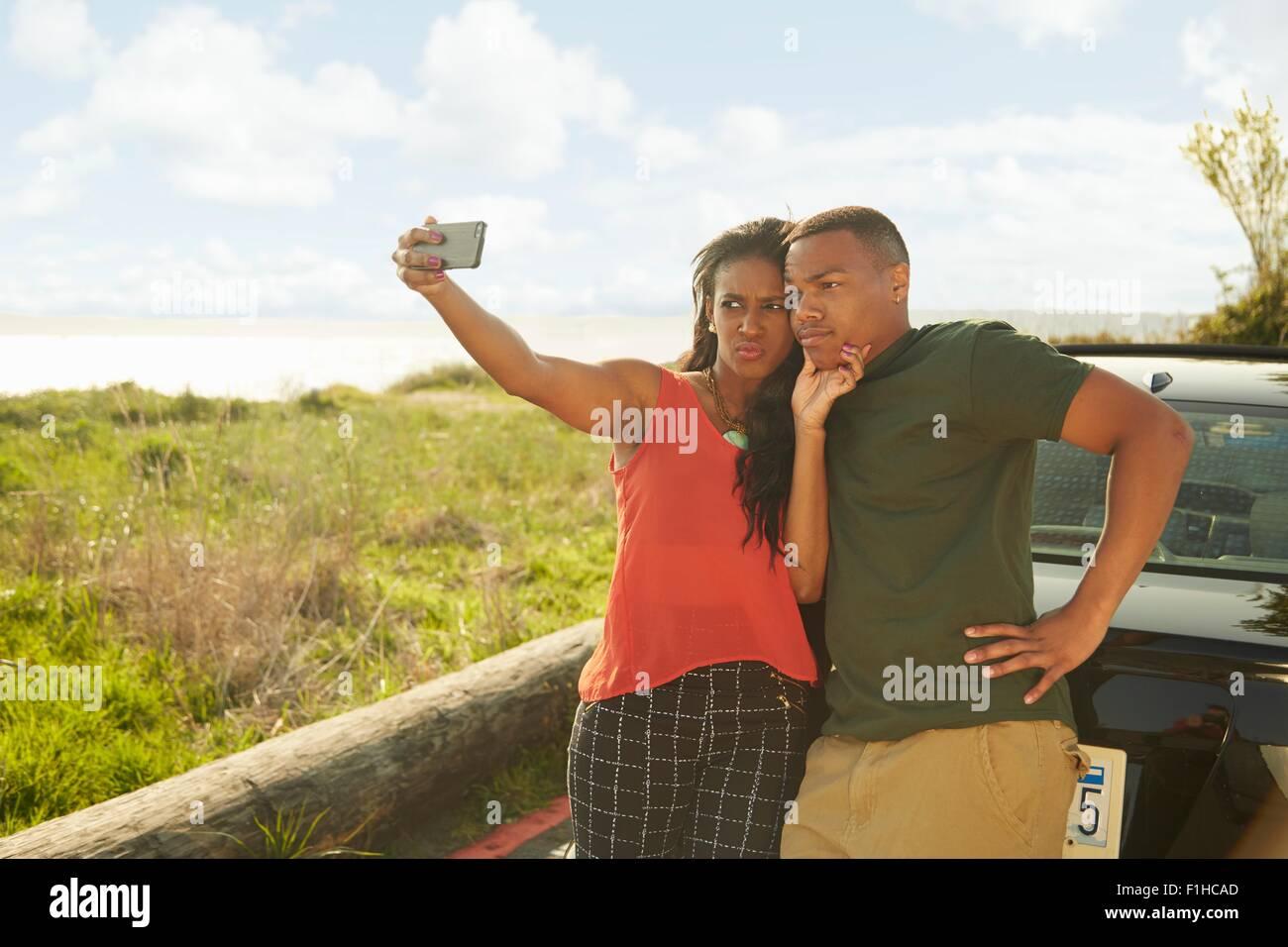 Coppia giovane utilizza lo smartphone tenendo selfie, rendendo le facce Immagini Stock