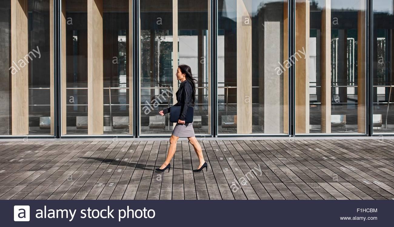 Imprenditrice a camminare lungo la facciata di vetro, Parigi, Île-de-France, Francia Immagini Stock