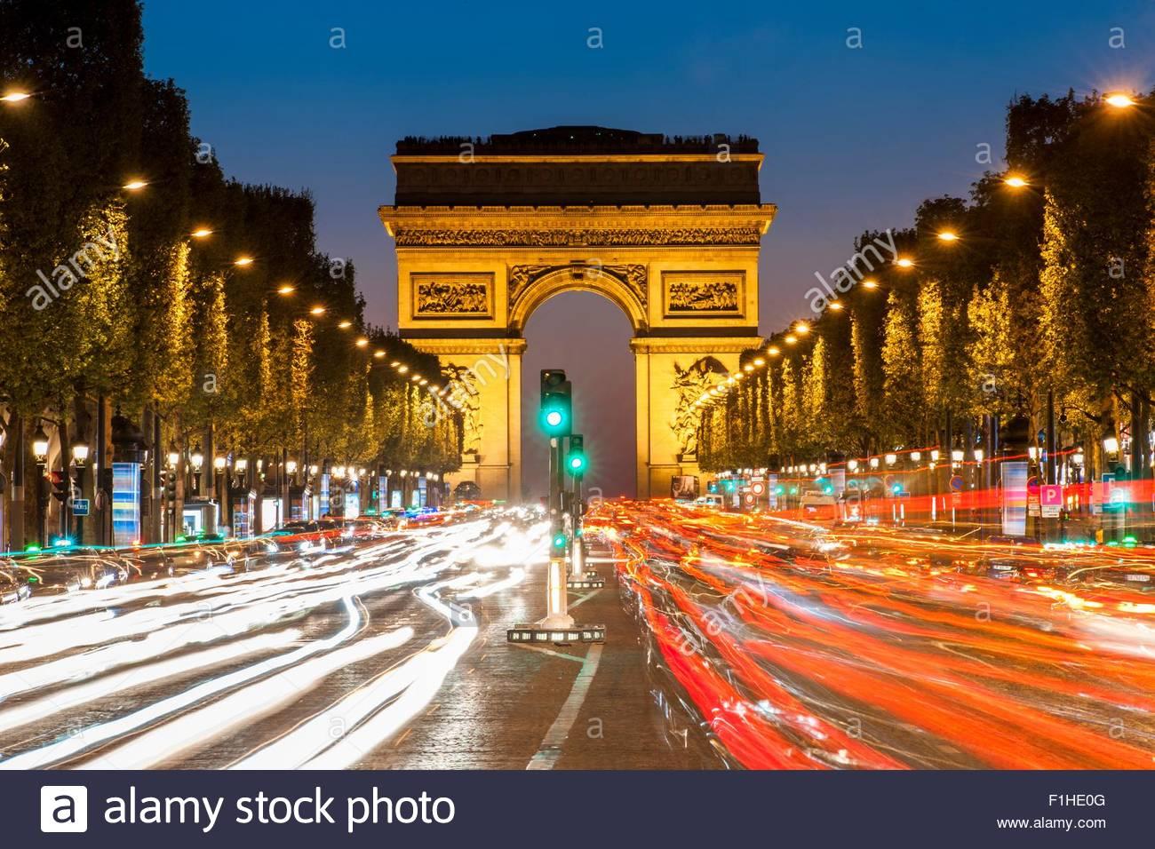 Vista del traffico nella parte anteriore del Arc de Triomphe di notte, Parigi, Francia Immagini Stock