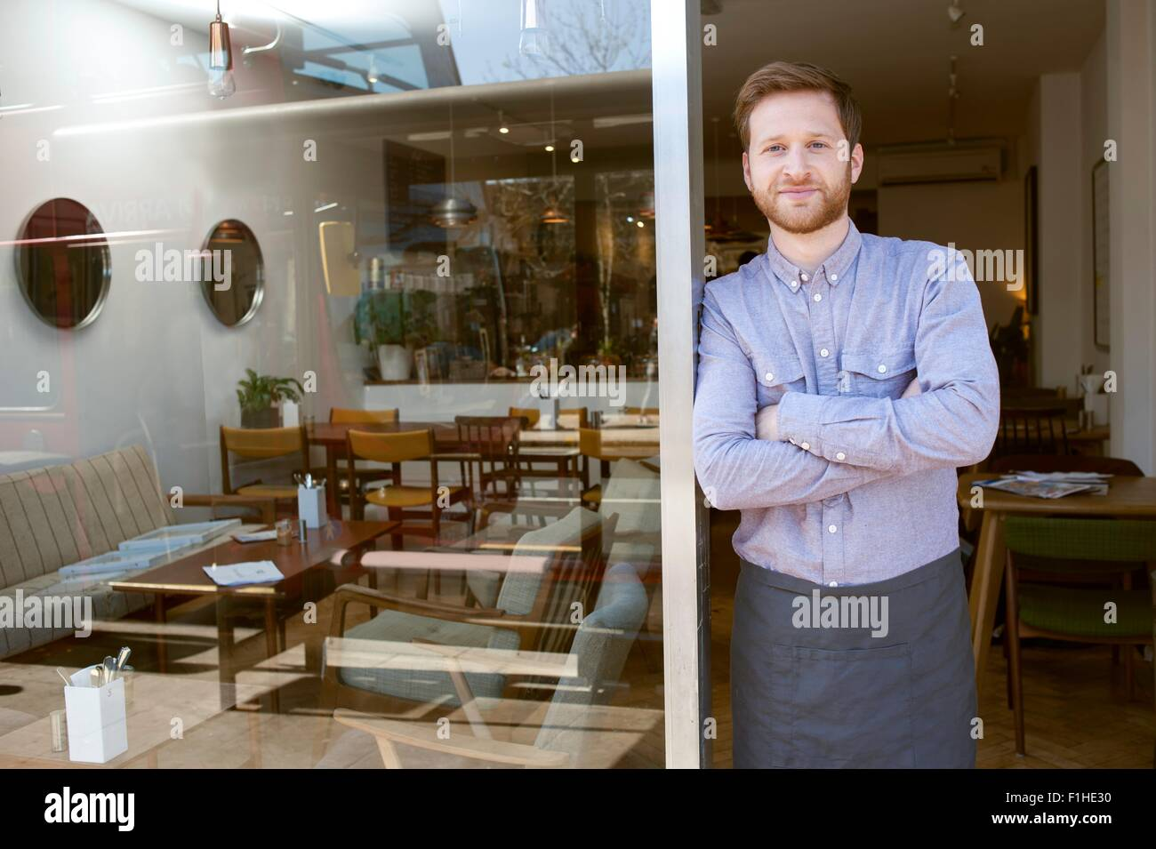 Ritratto di giovane maschio cafe proprietario con i bracci ripiegati in porta Immagini Stock