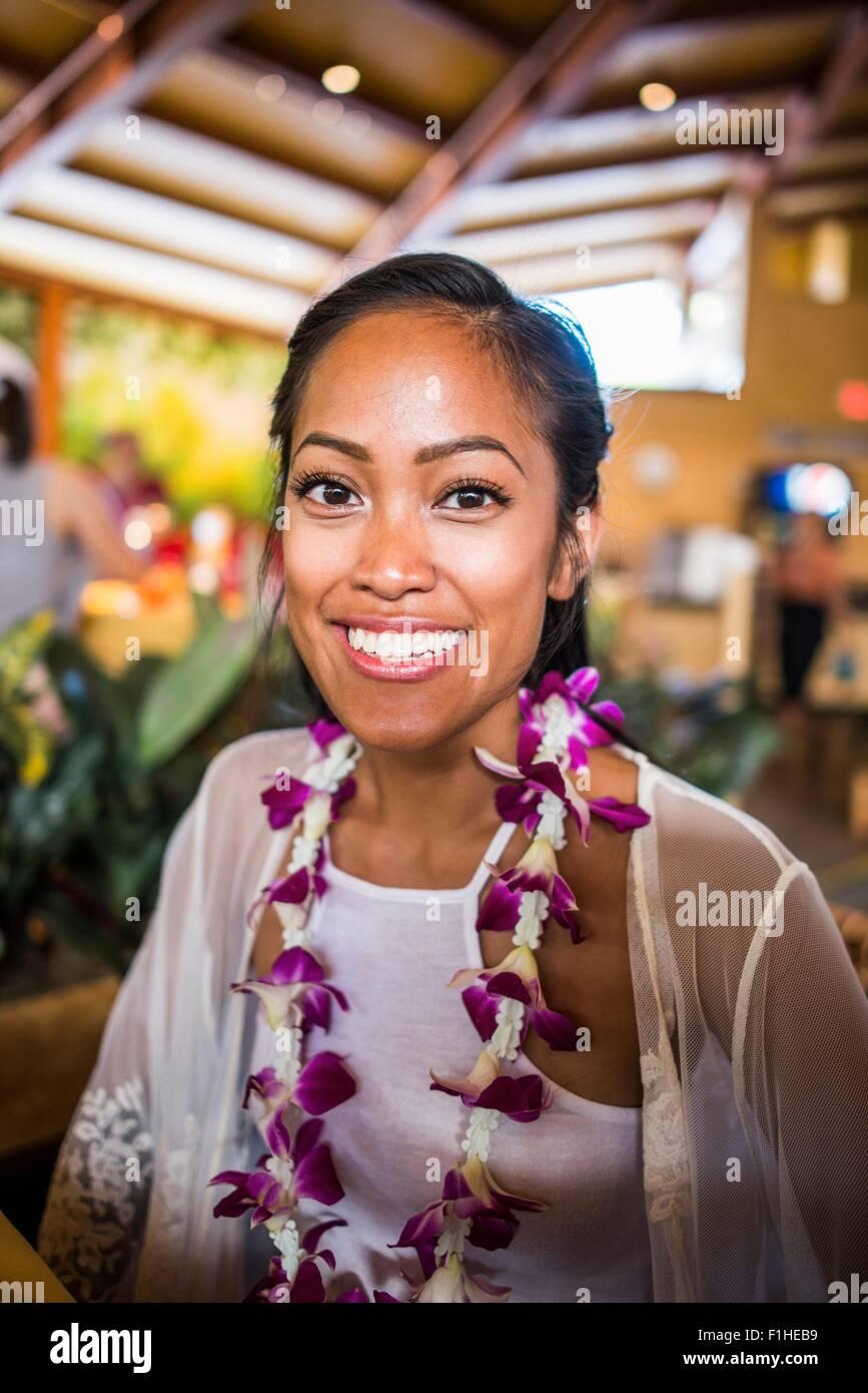Ritratto di giovane donna che indossa ghirlanda di fiori nel Centro Culturale Polinesiano, Hawaii, STATI UNITI D'AMERICA Immagini Stock