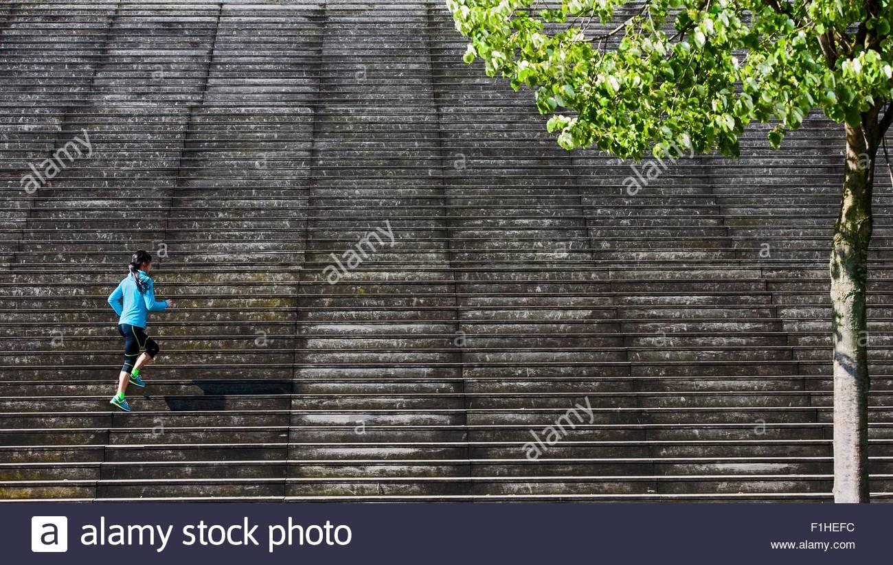 Vista in lontananza femminile che corre diagonalmente fino scala in legno Immagini Stock