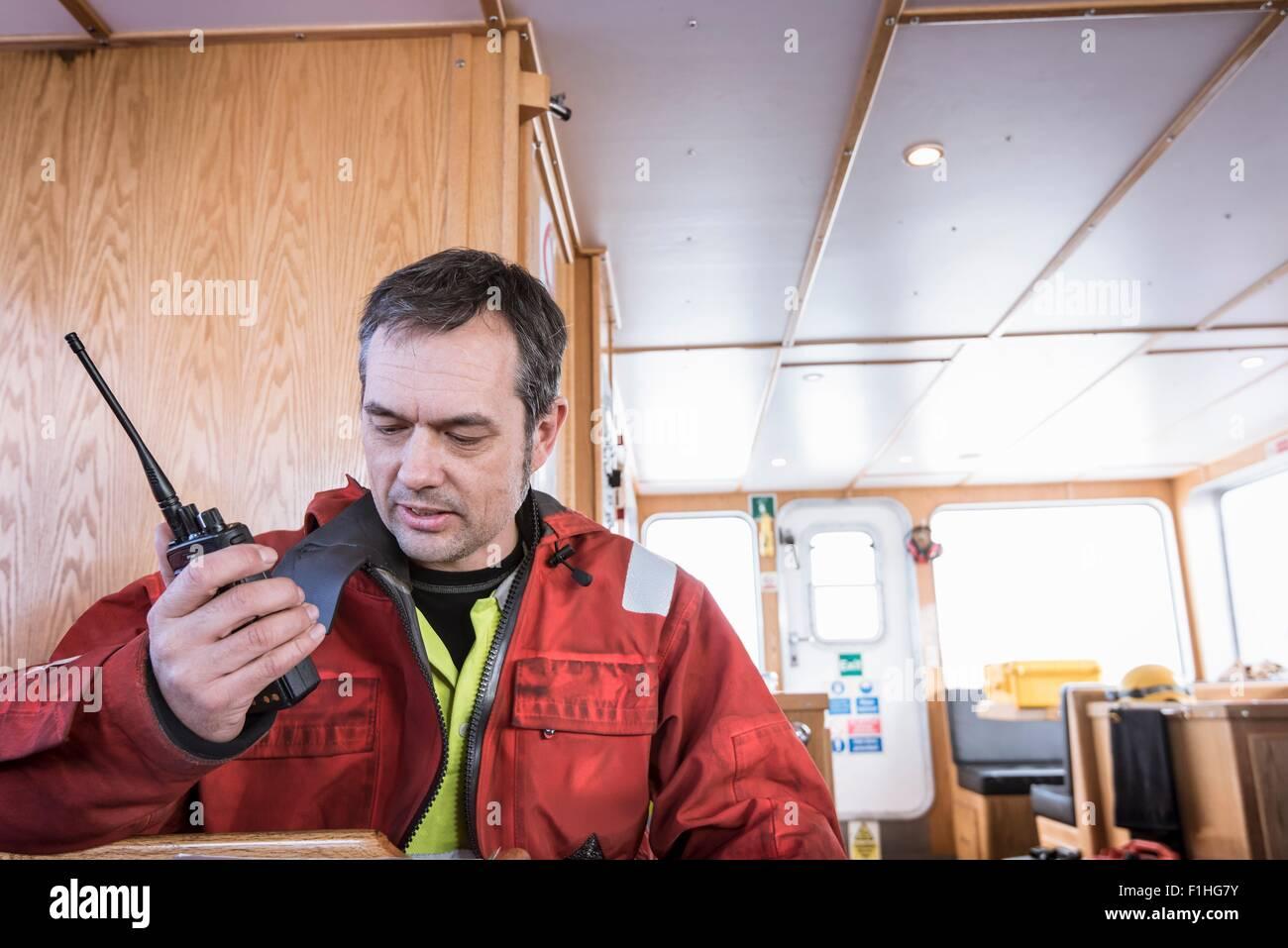 Tecnico su barca parlando a walkie talkie per ingegneri sulla turbina eolica a centrali eoliche offshore Immagini Stock