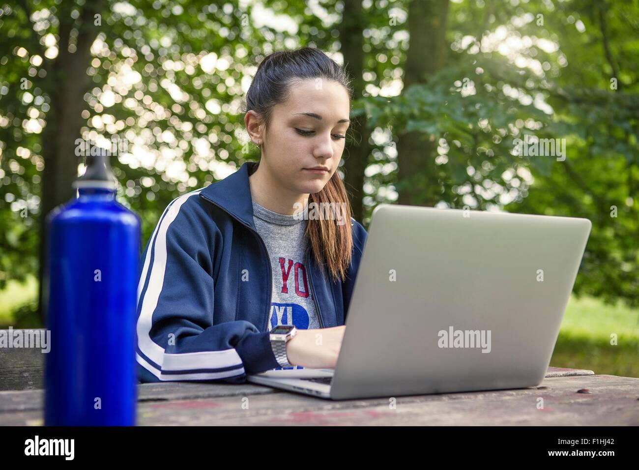 Ragazza adolescente in posizione di parcheggio con il portatile in panchina per picnic Immagini Stock