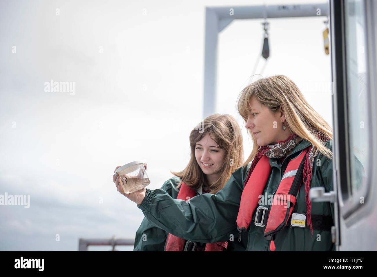 Scienziate ispezione campione di plancton sulla nave per la ricerca Immagini Stock