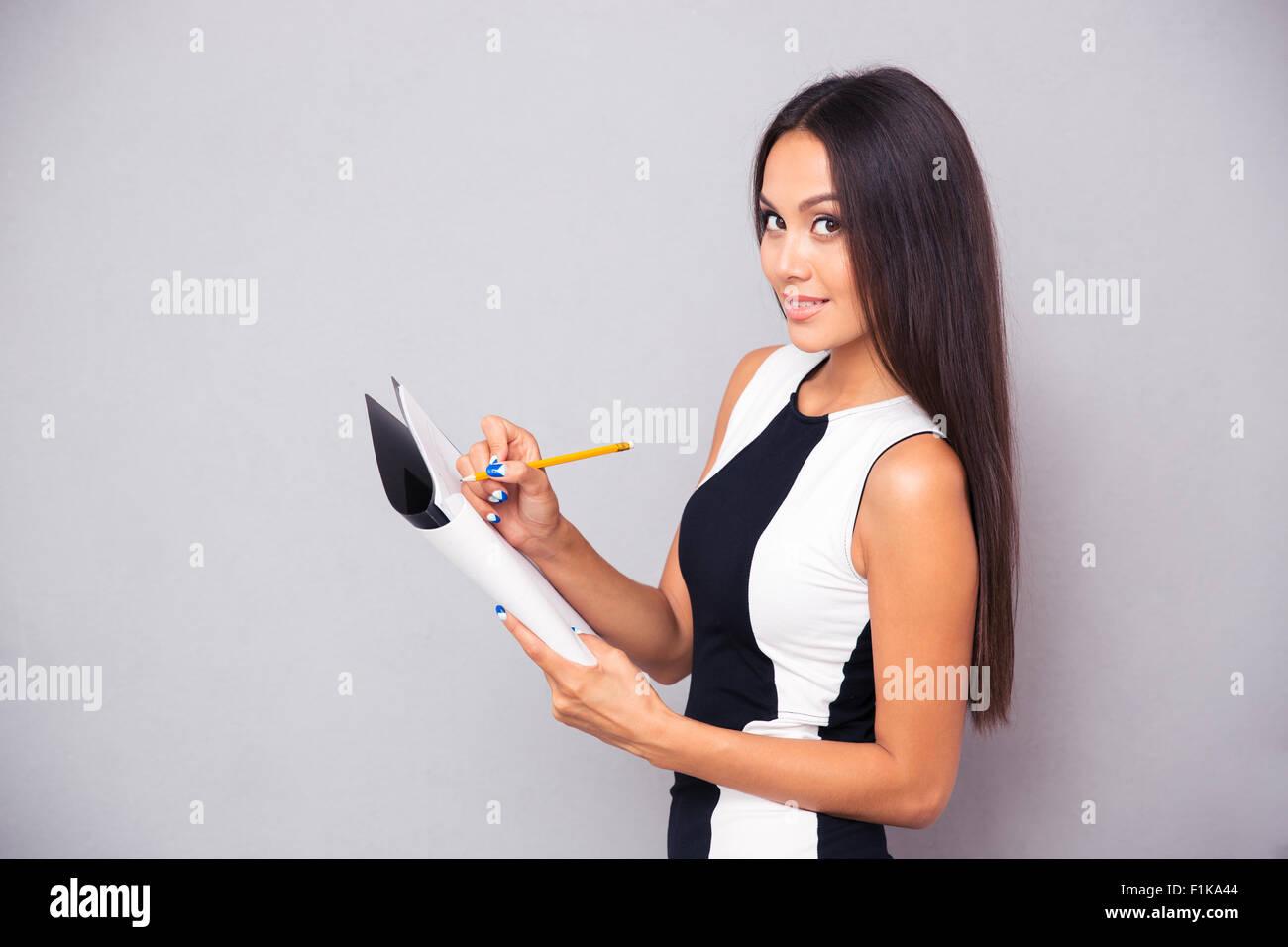 Ritratto di una donna felice scrivere appunti nel Blocco note su sfondo grigio e guardando la fotocamera Immagini Stock