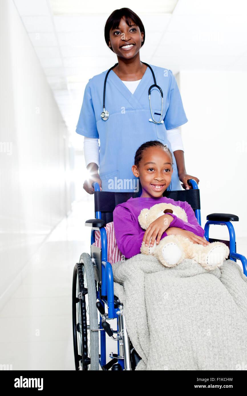 Un medico spingendo una ragazza con un orsacchiotto in una sedia a rotelle Immagini Stock