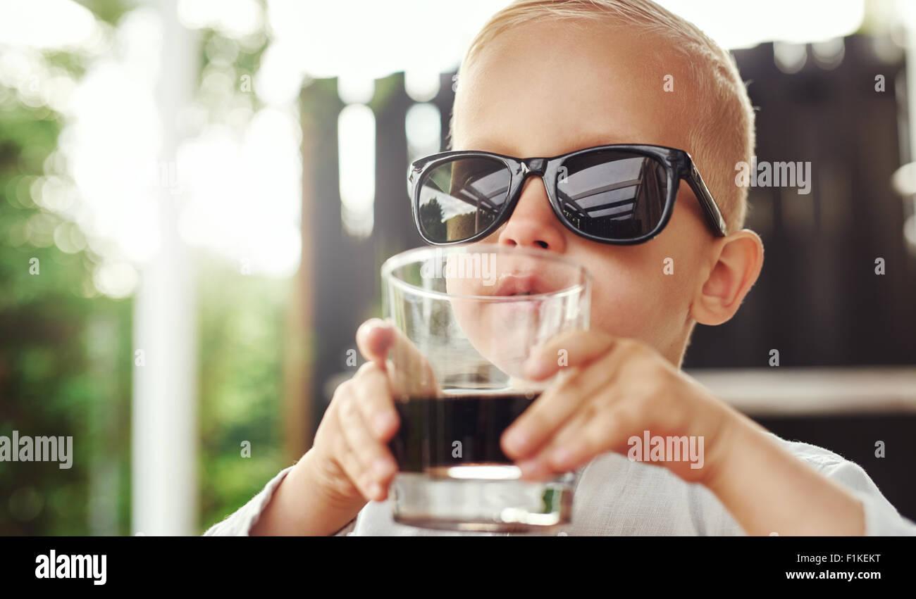 Carino hipster ragazzino su occhiali da sole dimensioni appartenenti alla madre o al padre seduto sorseggiando una Immagini Stock