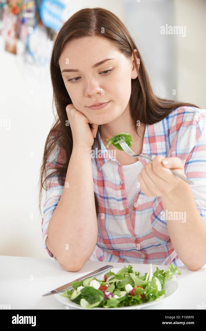 Ragazza adolescente sulla dieta mangiare piatto di insalata Immagini Stock