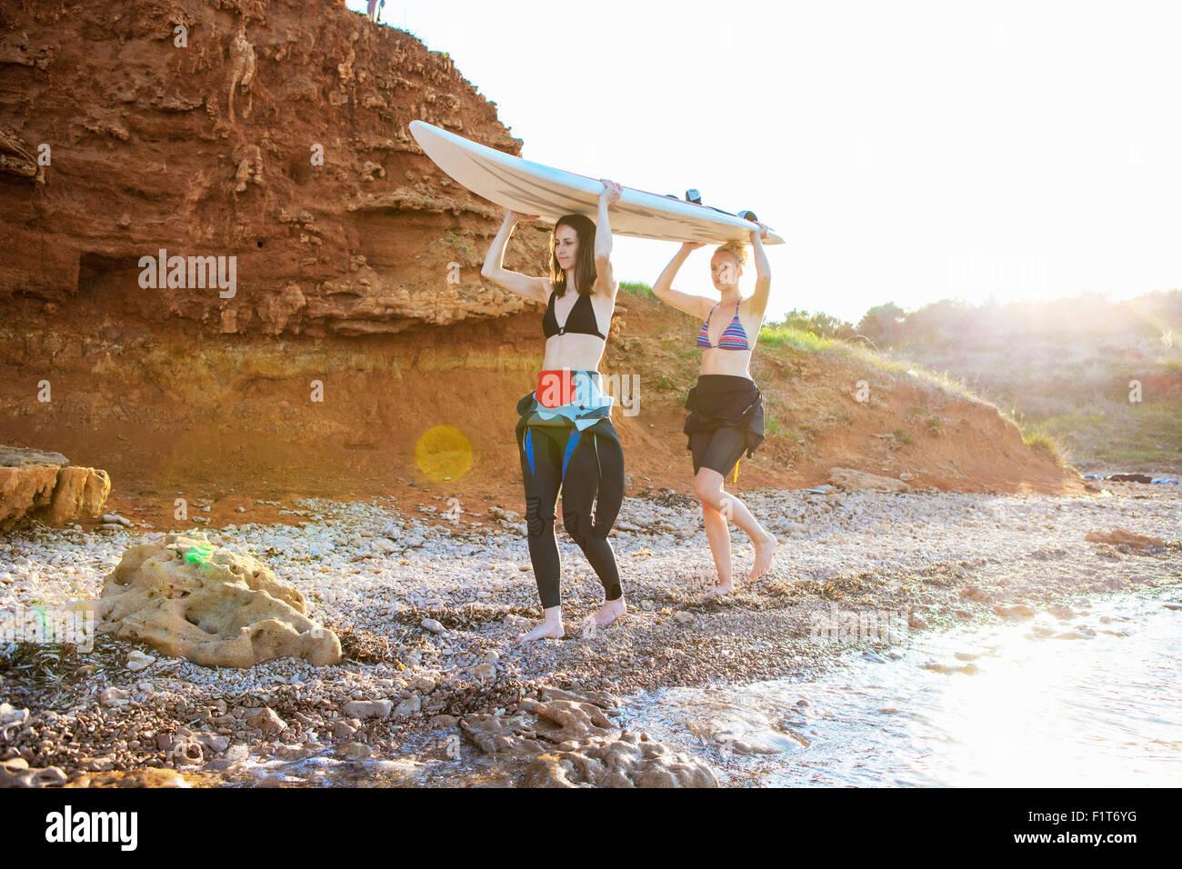 Femmina di surfers che trasportano le tavole da surf Immagini Stock