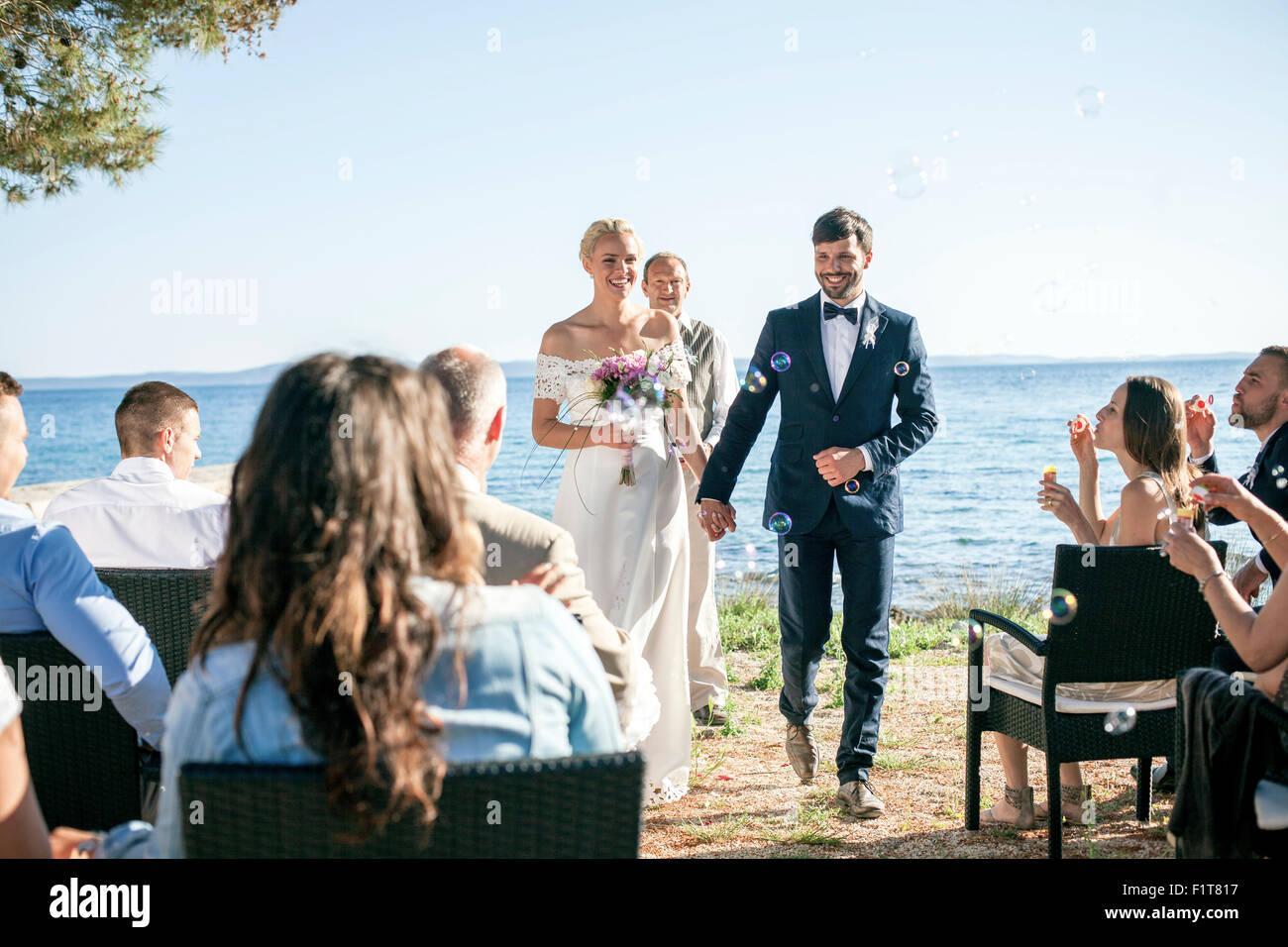Sposa e lo sposo alla cerimonia di nozze sulla spiaggia Immagini Stock 7912a89c958d