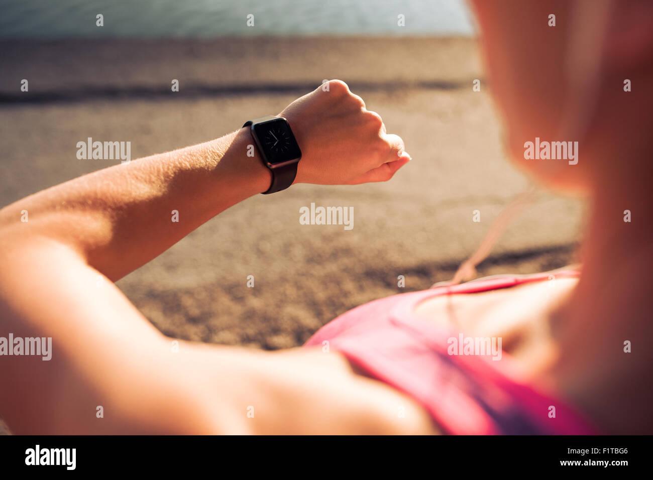 Closeup colpo di giovani pareggiatore femmina pronto per funzionare insieme e guardando sport smartwatch. Donna Immagini Stock