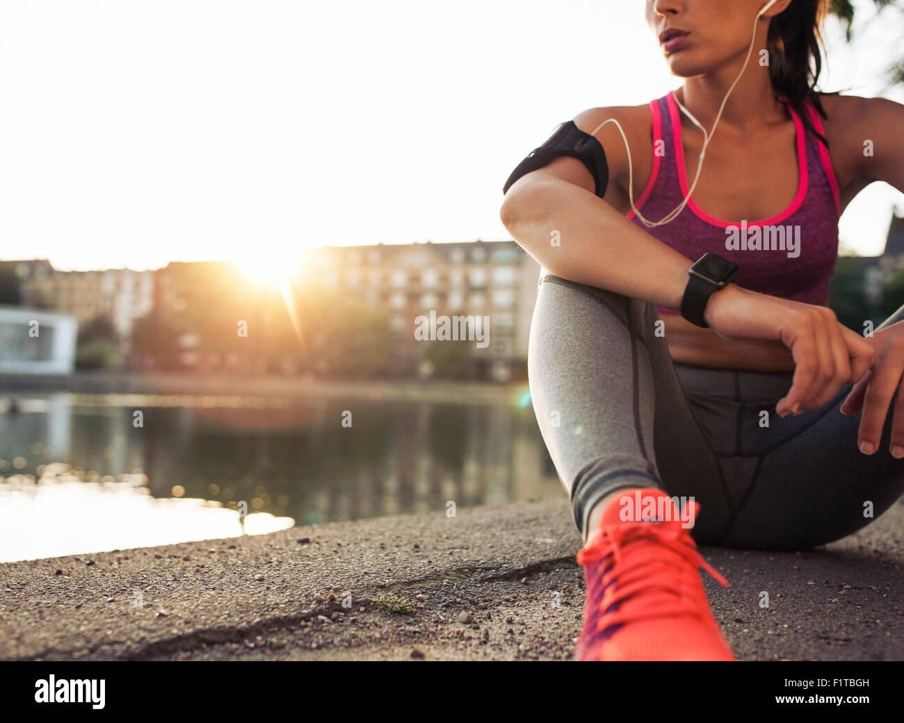 Giovane donna runner riposo dopo la sessione di allenamento sulla mattina di sole. Femmina modello fitness seduta Immagini Stock