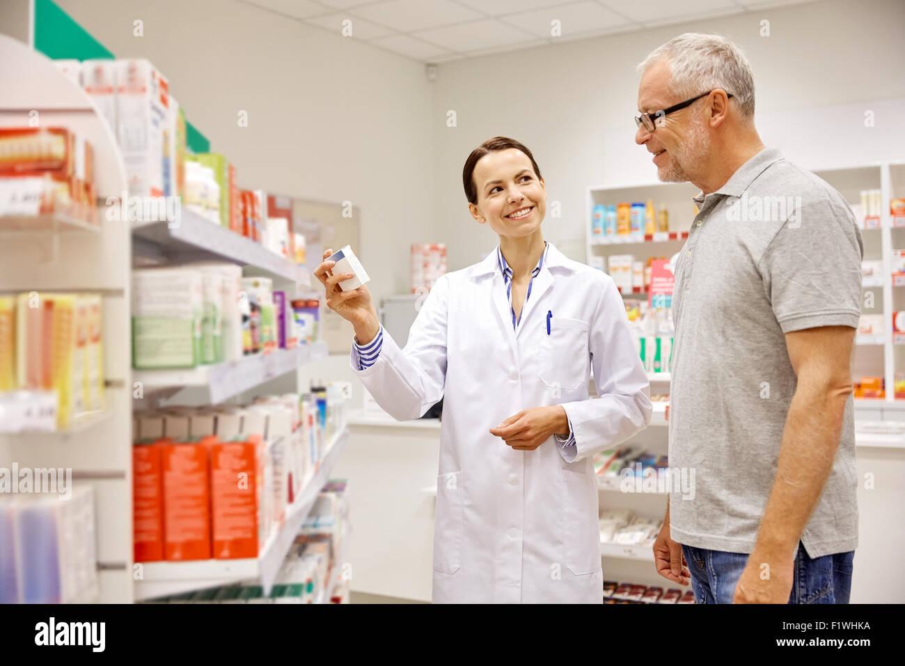 Il farmacista che mostra il farmaco per senior uomo in farmacia Immagini Stock