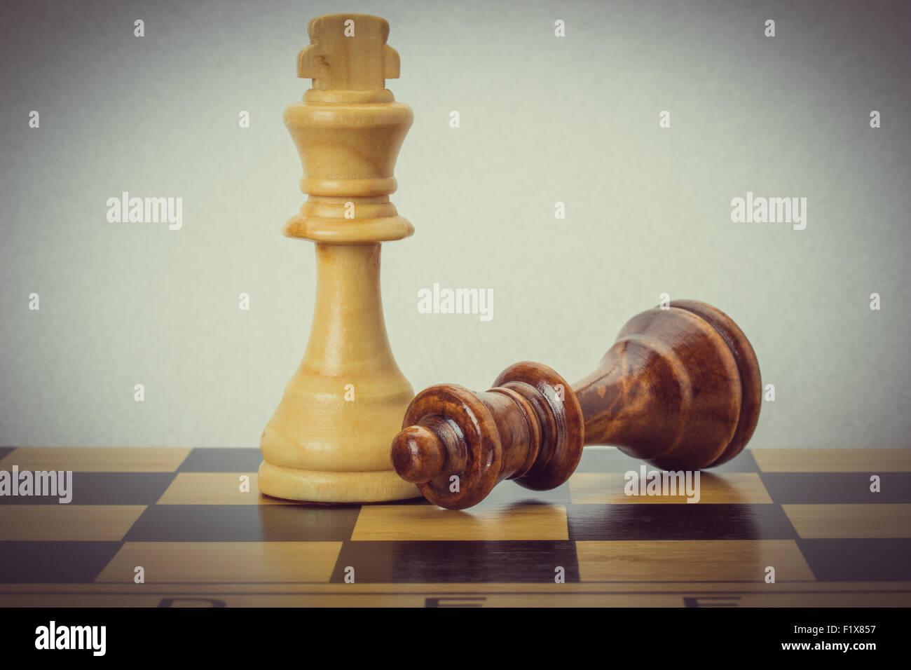 Scacchi in legno sulla scacchiera. Immagini Stock