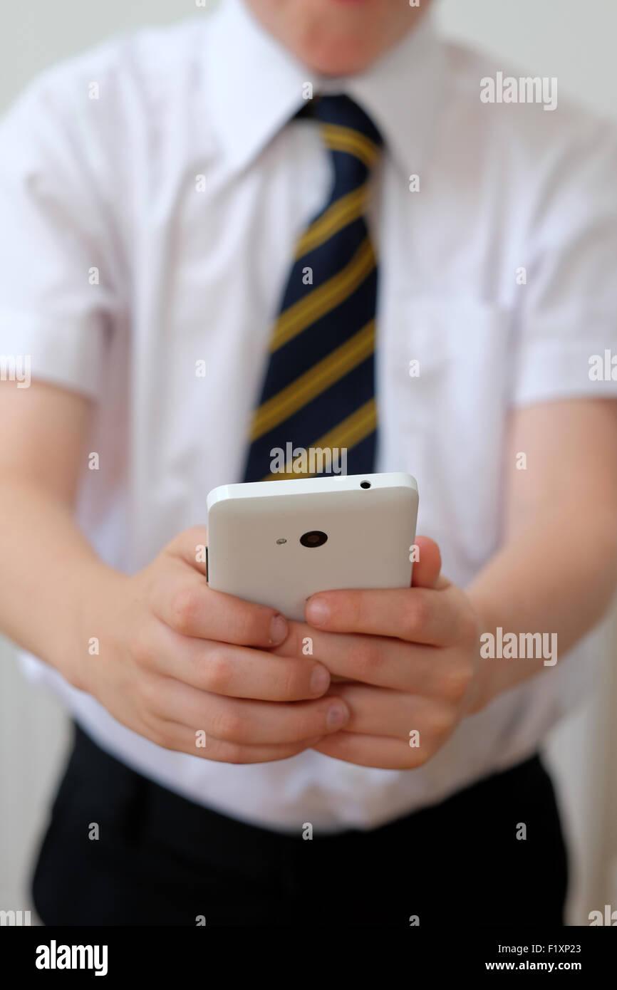 Una scuola per bambini in uniforme utilizzando il suo telefono cellulare ( texting ) REGNO UNITO Immagini Stock