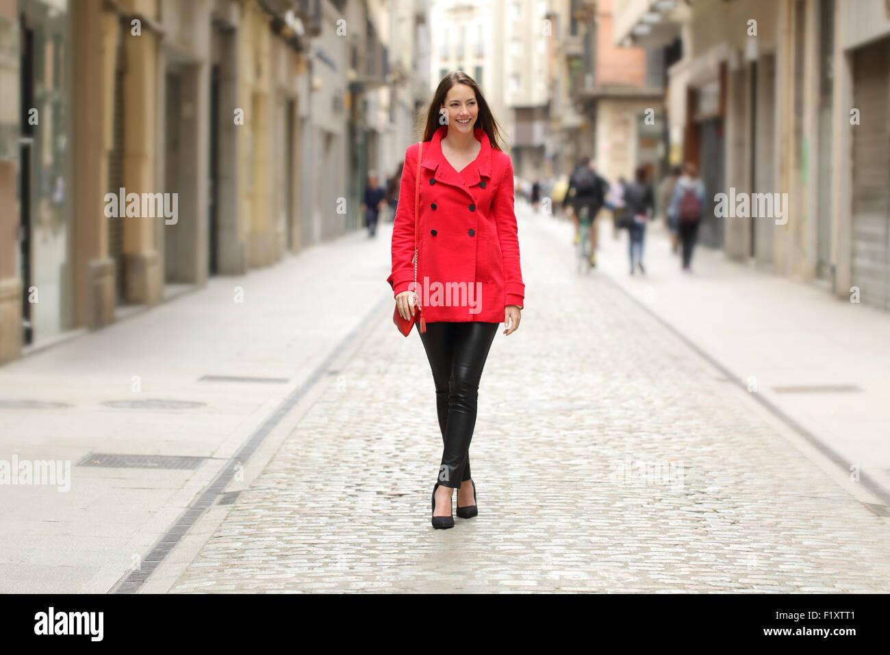 Felice bella moda donna in cappotto di pelle che cammina sulla strada della città