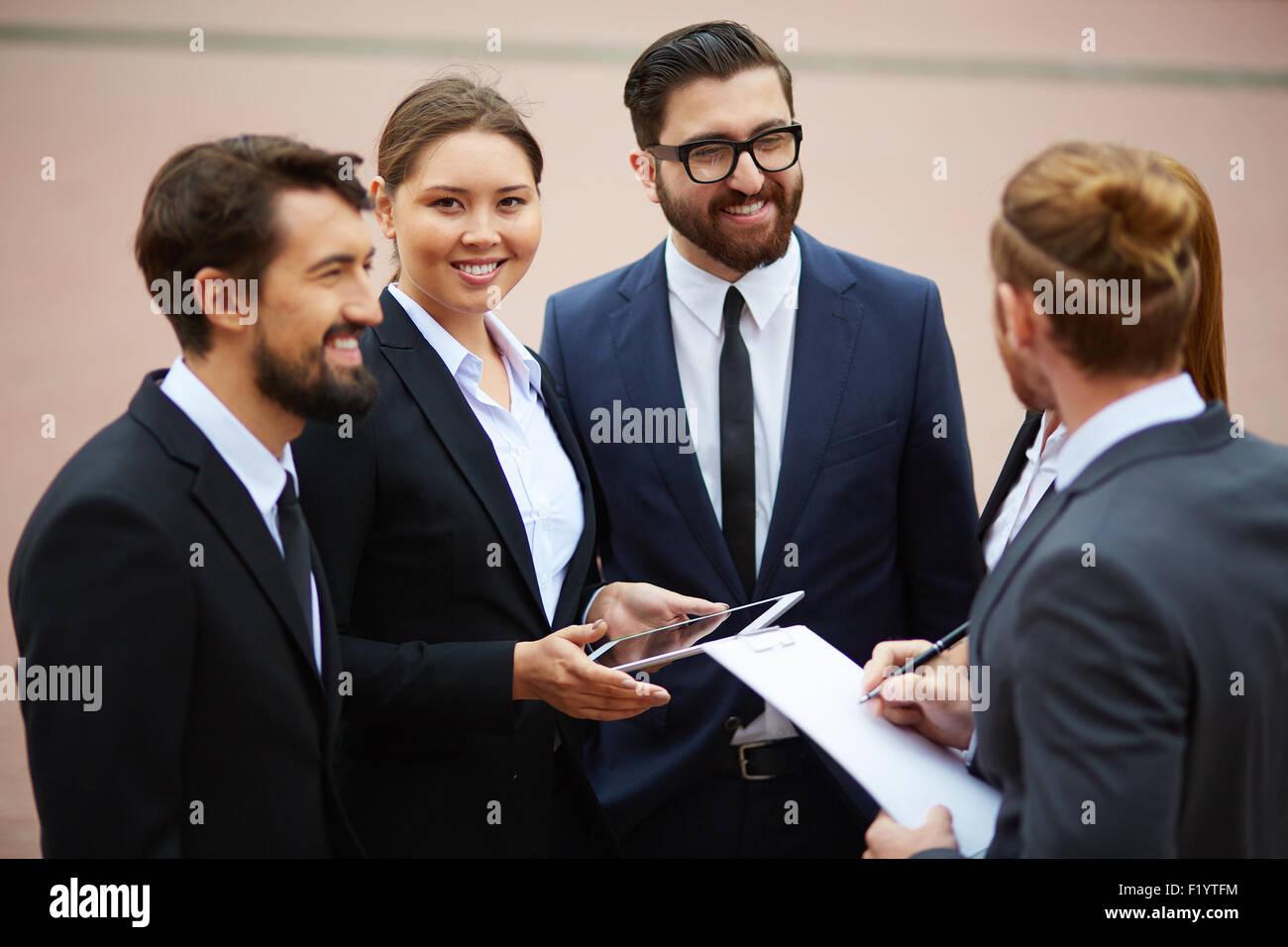 Felice imprenditrice guardando la fotocamera durante il parlare con i colleghi Immagini Stock