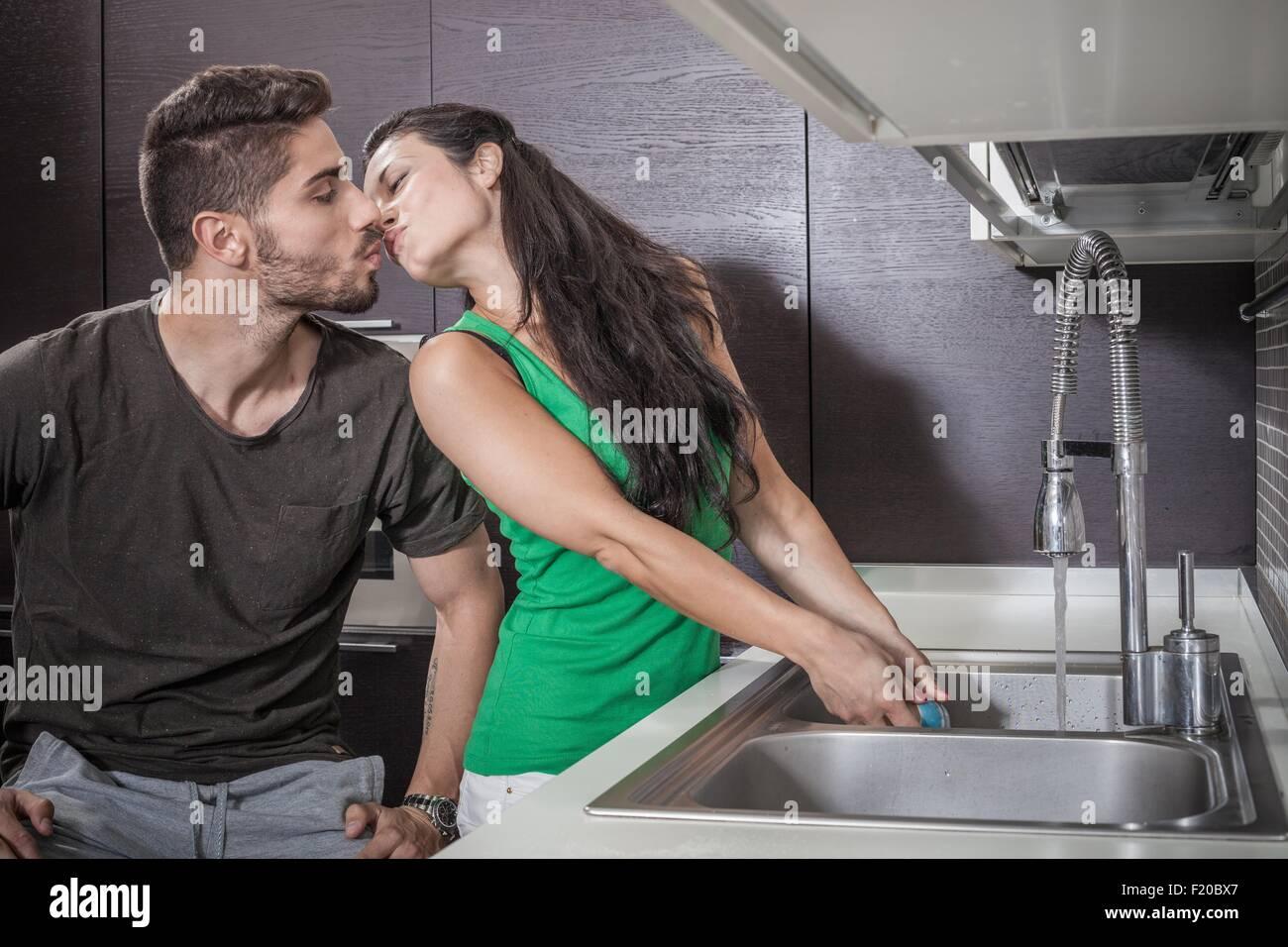 Giovane donna lavaggio fino mentre baciare Ragazzo Immagini Stock