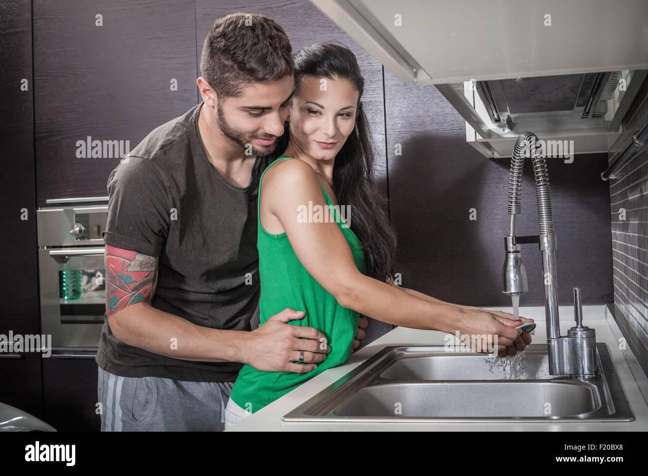 Giovane donna lavaggio fino pur essendo abbracciata dal fidanzato Immagini Stock