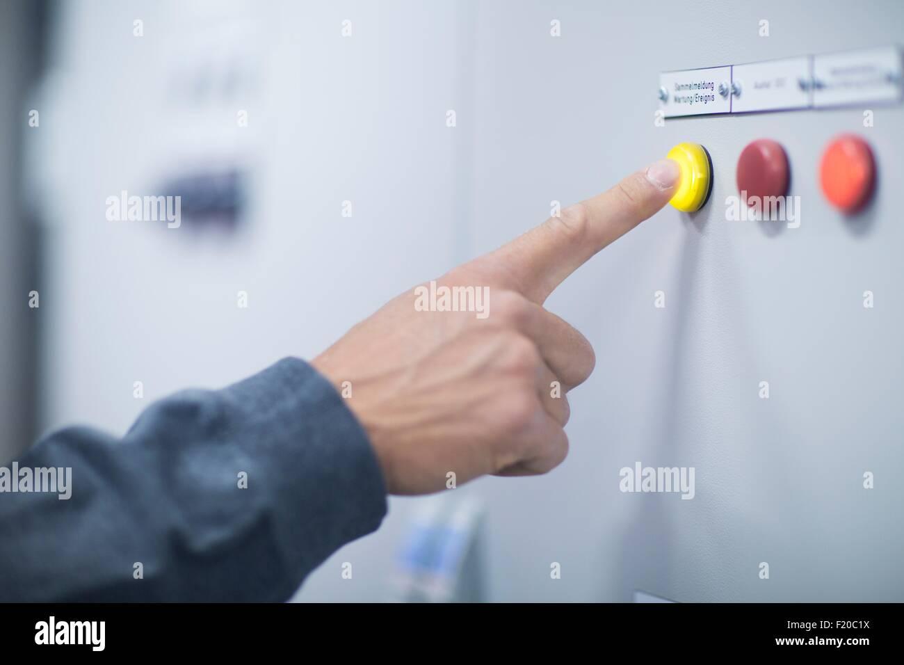 Mano del tecnico maschio premendo il tasto giallo sul pannello di controllo Foto Stock