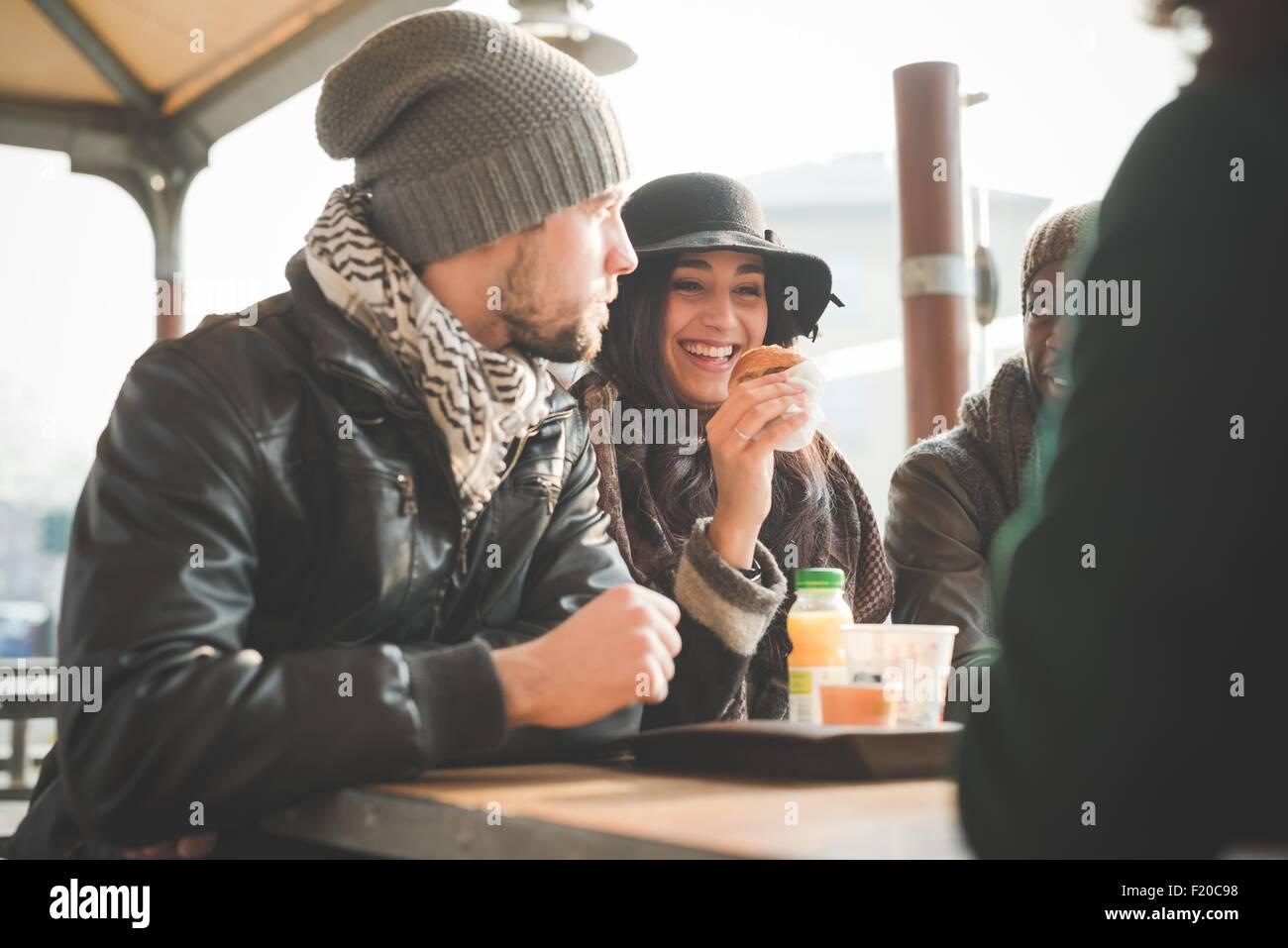 Quattro giovani amici adulti in chat e mangiare le ciambelle al cafè sul marciapiede Immagini Stock