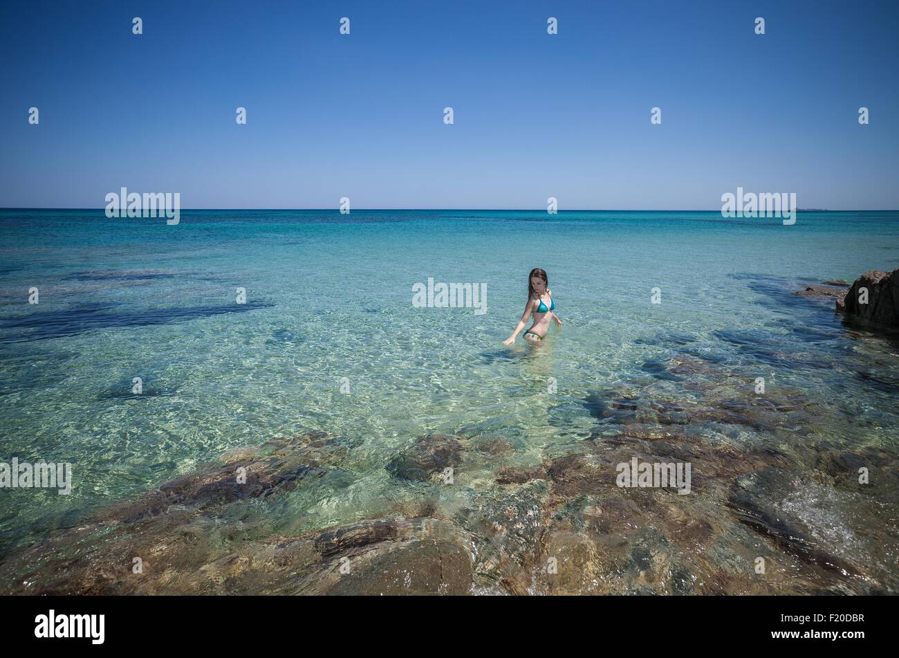 Giovane donna che indossa un bikini guadare in mare, Cagliari, Sardegna, Italia Immagini Stock