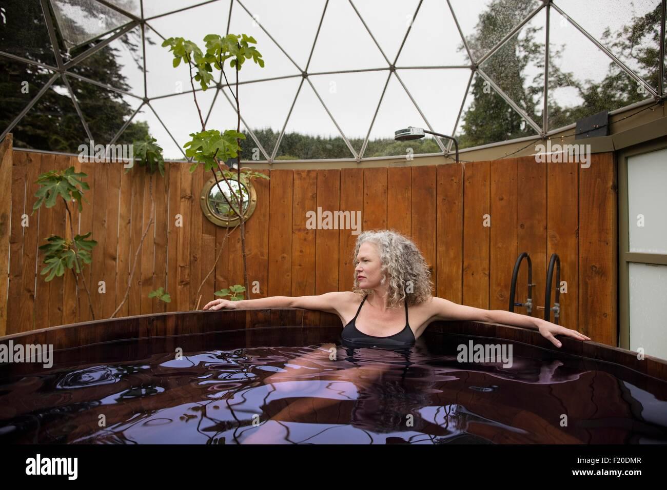 Donna matura relax nella vasca calda al rifugio eco Immagini Stock
