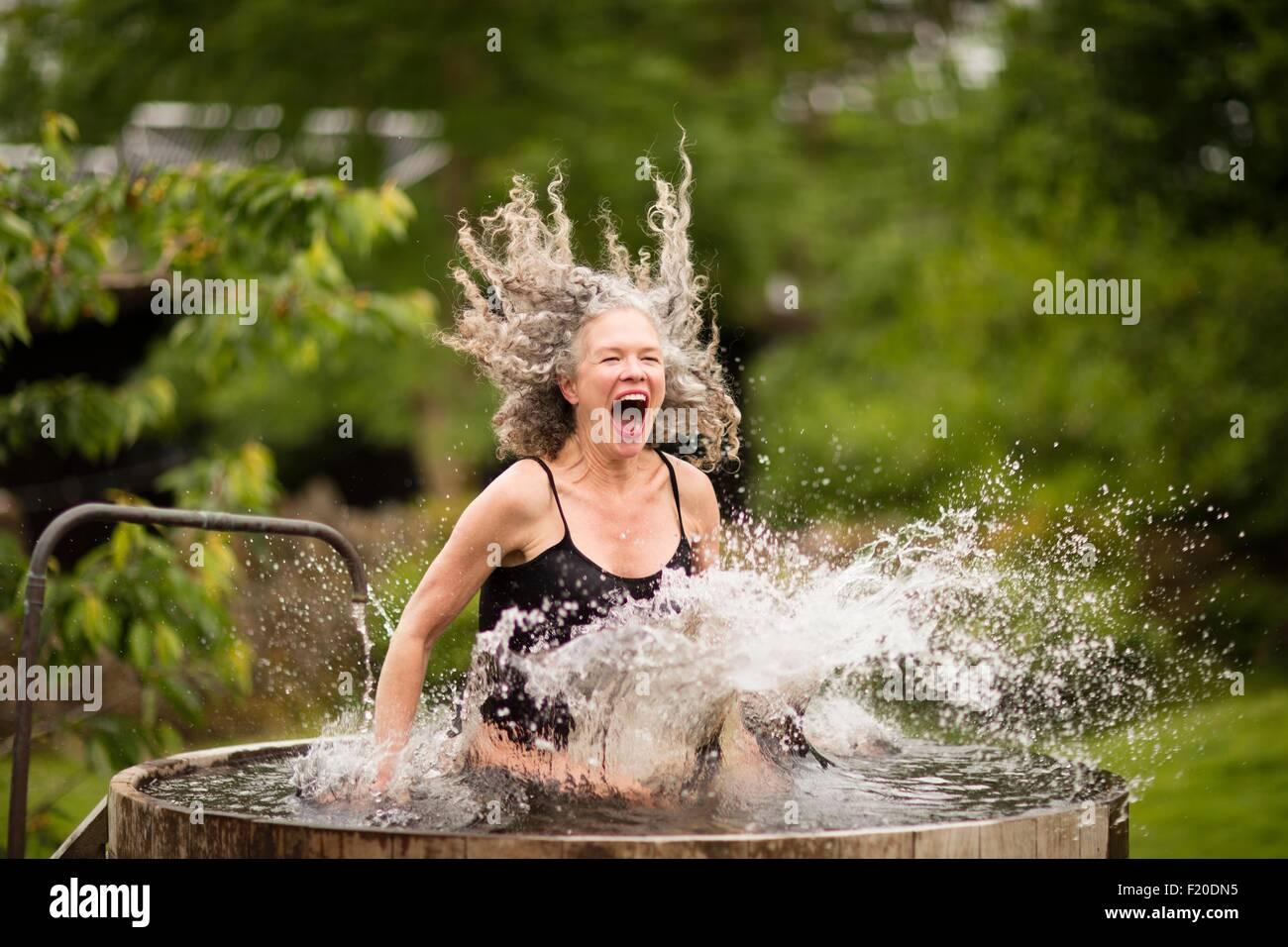 Donna matura schizzi in acqua fredda vasca al rifugio eco Immagini Stock