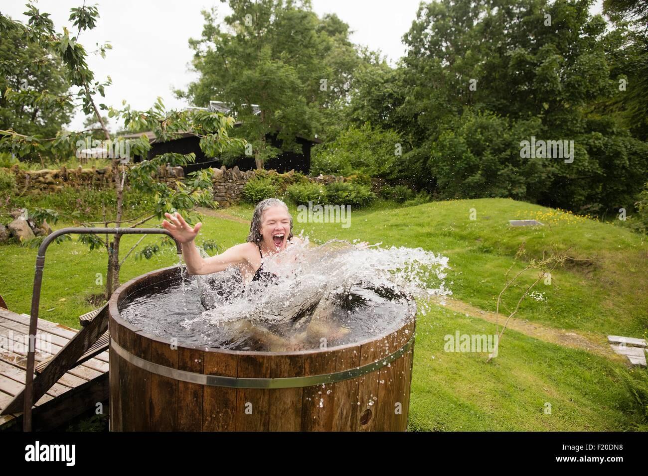 Donna matura saltando in acqua fredda vasca al rifugio eco Immagini Stock