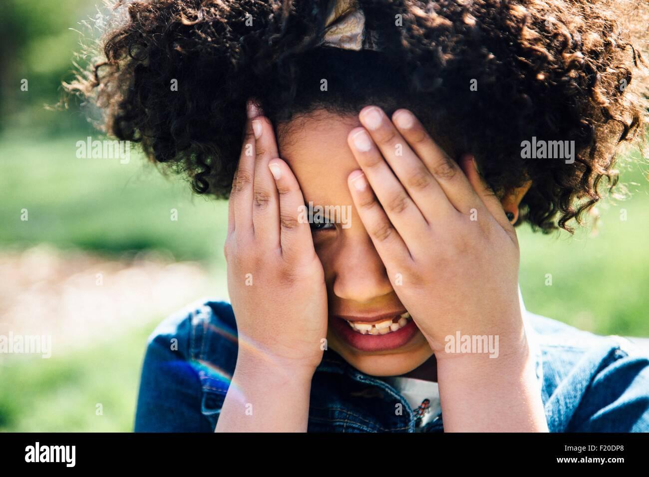 Close up ritratto della ragazza che ricopre la faccia con le mani Immagini Stock