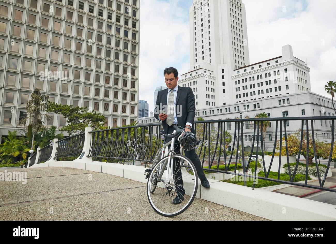 Uomo d affari sulla passerella elevata con bicicletta guardando smartphone, Los Angeles City Hall, CALIFORNIA, STATI Immagini Stock
