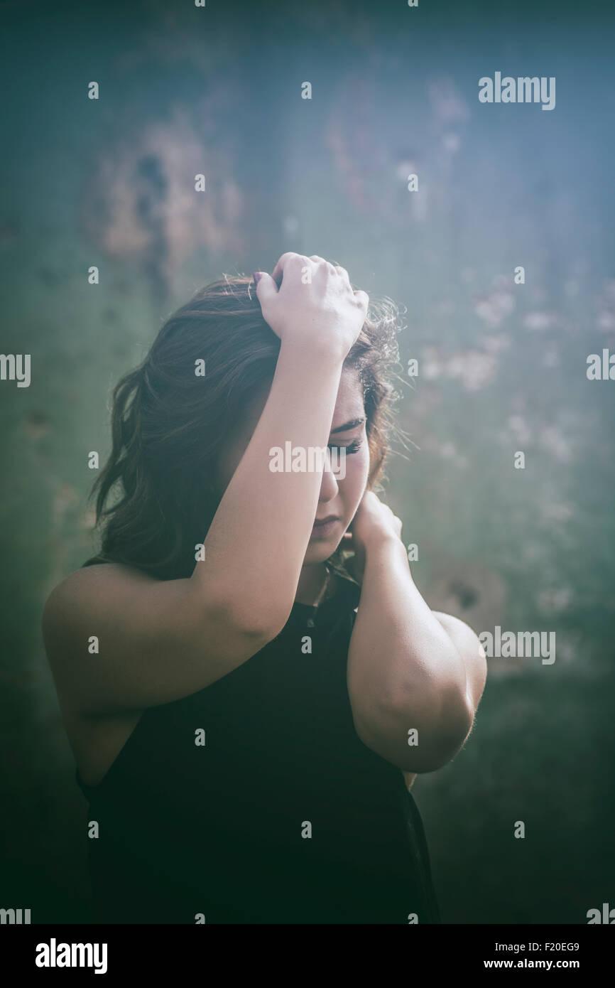 Spaventata donna nasconde il viso con le mani Foto Stock