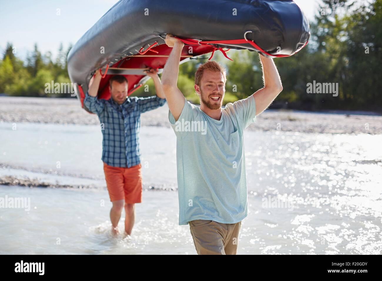 Due uomini che trasportano dinghy sopra le loro teste attraverso il fondale basso Immagini Stock