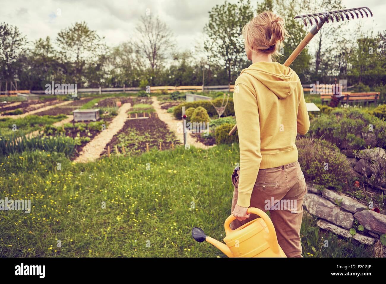 Donna matura, giardinaggio, portando rastrello e annaffiatoio, vista posteriore Immagini Stock