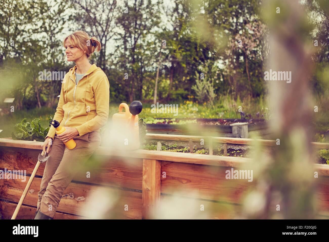 Donna matura, appoggiata contro la recinzione, prendendo una pausa da giardinaggio, tenendo cazzuola e acqua in Immagini Stock