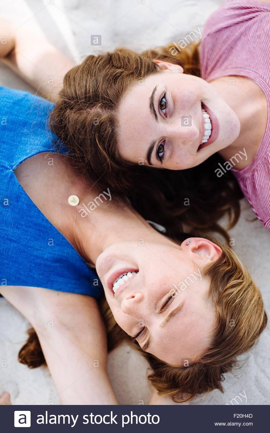 Ritratto di overhead di due giovani amici di sesso femminile che giace sulla spiaggia Immagini Stock