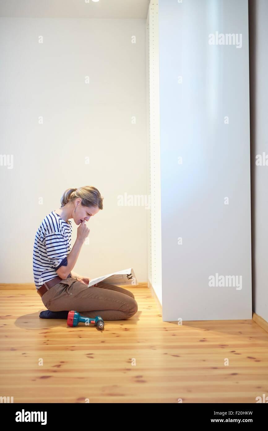 Donna matura in ginocchio e leggere il manuale di istruzioni per l'armadio flatpack Immagini Stock