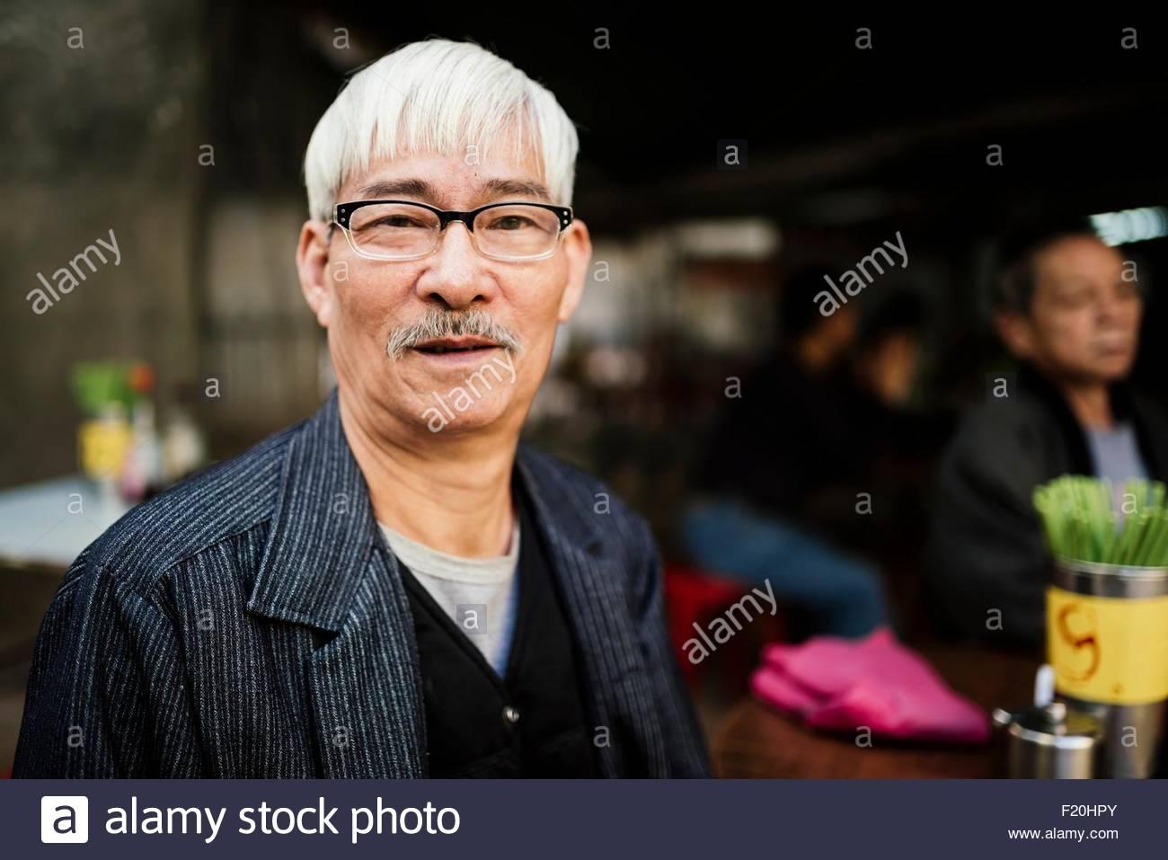 Ritratto di uomo anziano con i capelli grigi che indossano occhiali guardando la fotocamera Immagini Stock