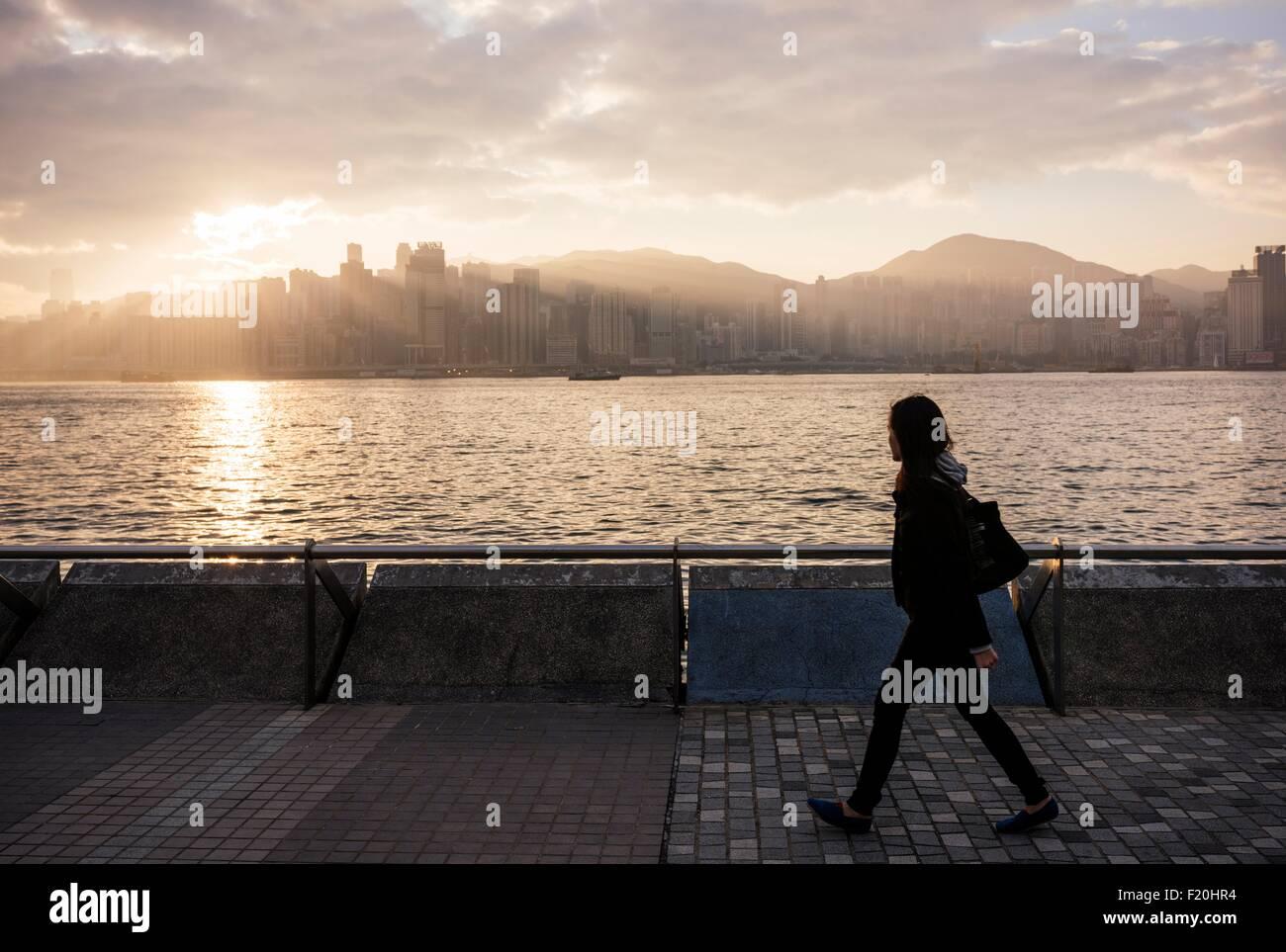 Vista laterale della giovane donna a piedi acqua passata, Hong Kong, Cina Immagini Stock