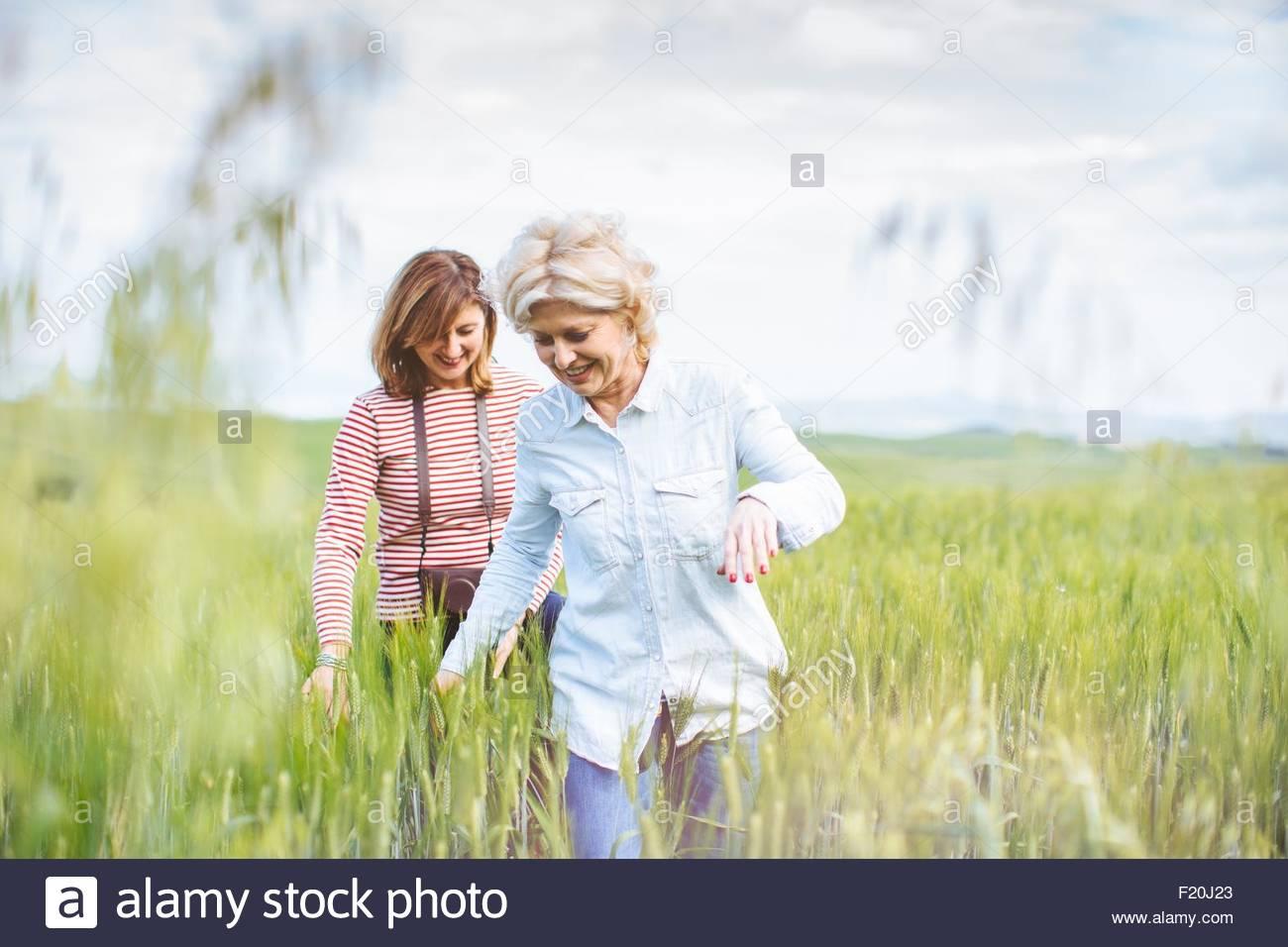 Due femmina matura amici camminando in wheatfield, Toscana, Italia Immagini Stock