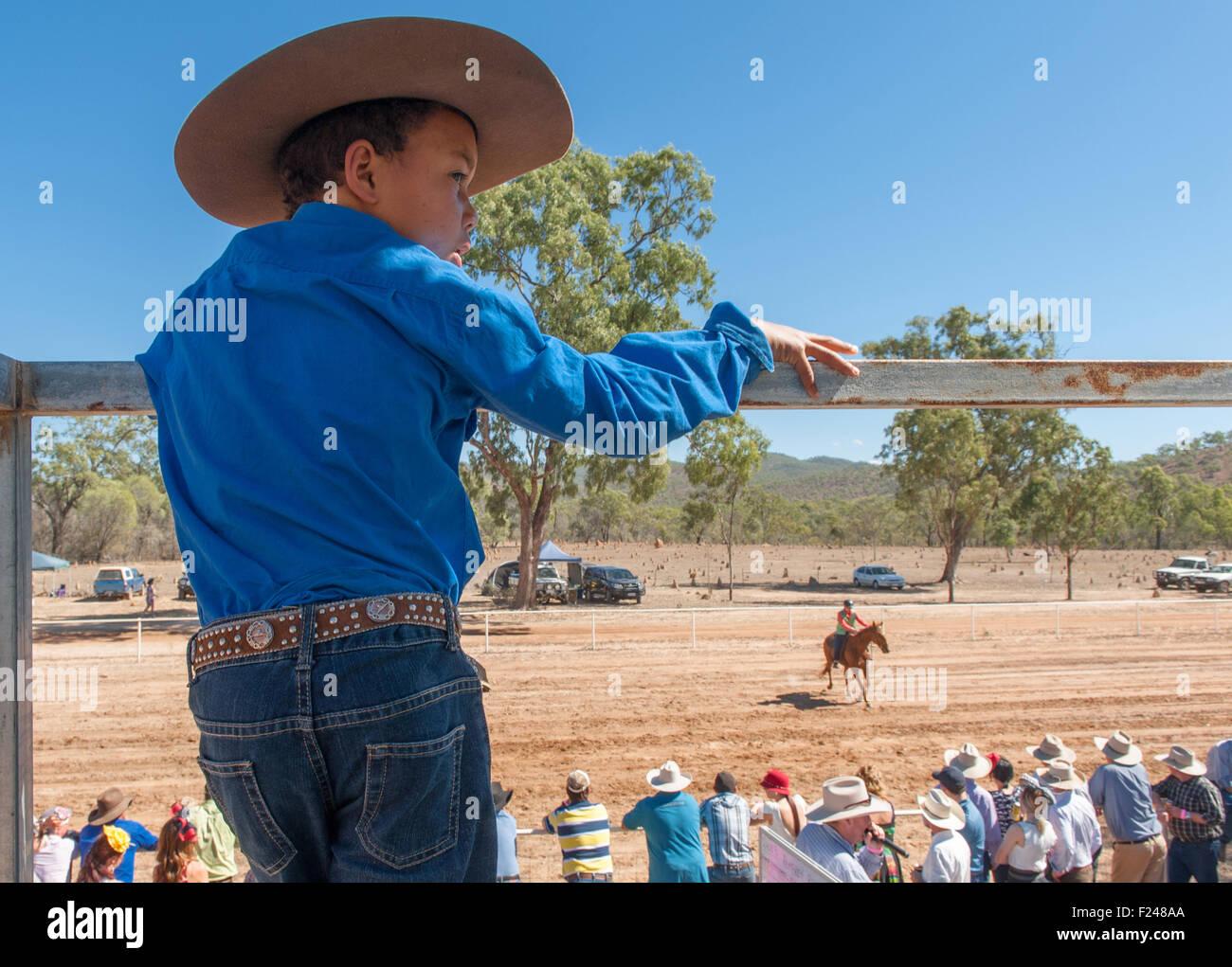 Ragazzo giovane guardando la bussola le gare a Eureka Creek Rodeo a fine luglio, il Queensland del Nord, Australia Immagini Stock