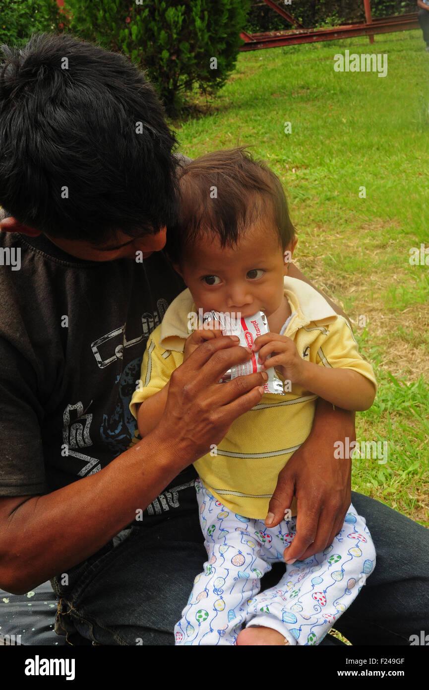 Guatemala, San Cristobal, bambino seduto sul ginocchio del padre e mangiare plumpy dado (Cristobal Pop Calel 23, Immagini Stock